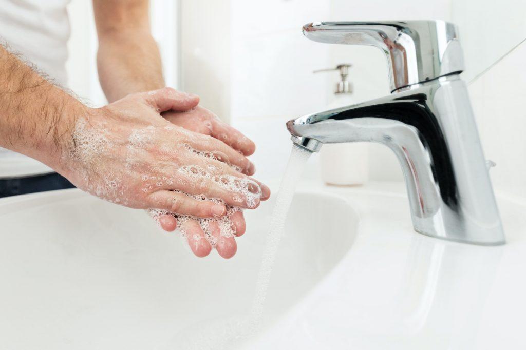 Henkilö puhdistaa kätensä veishanan alla